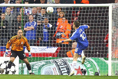 Joe Cole (R) takes a shot on goal against Liverpool's goalkeeper Jose Reina.