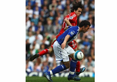 Stephen Kelly of Birmingham City tussles for possession with Yossi Benayoun of Liverpool