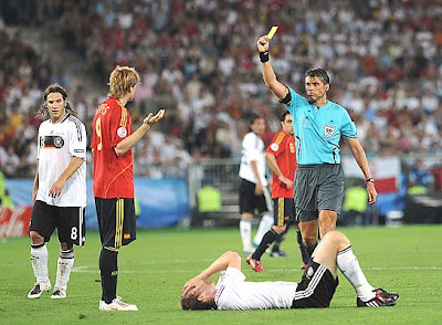 Italian referee Roberto Rosetti gives Spanish forward Fernando Torres (2nd L) a yellow card as German defender Per Mertesacker lays on the pitch injured.