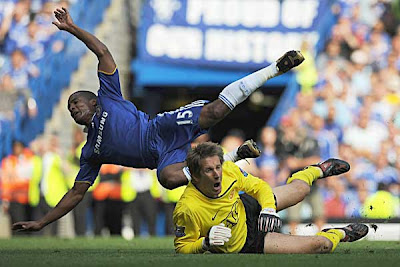 Manchester United goalkeeper Edwin van der Sar collides with Florent Malouda of Chelsea. Van der Sar left the field soon afterwards, struggling with an injury.<br />
