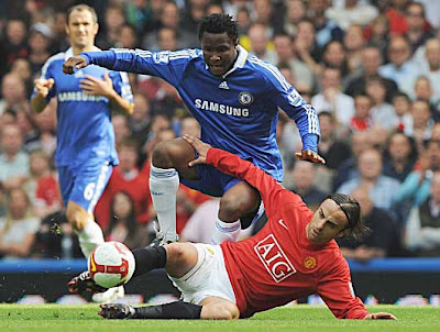 Dimitar Berbatov of Manchester United tackles John Obi Mikel of Chelsea.