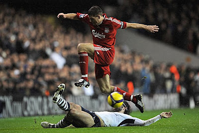 Steven Gerrard of Liverpool hurdles the challenge from Vedran Corluka of Tottenham.