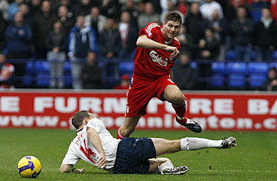 Liverpool midfielder Steven Gerrard (left) avoids a tackle from Bolton Wanderers forward Kevin Davies during their English Premier League football match at The Reebok Stadium in Bolton, north west England
