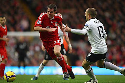 Jamie Carragher of Liverpool chases the ball under pressure from Danny Murphy of Fulham. The game ended in a 0-0 draw