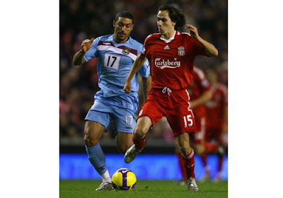 Yossi Benayoun of Liverpool surges away from Hayden Mullins of West Ham United