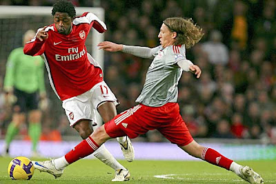 Arsenal's Alex Song (left) is tackled by Liverpool's Lucas Leiva.