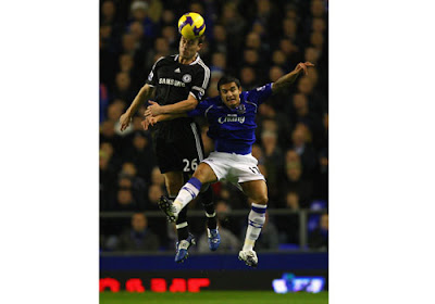 John Terry of Chelsea beats Tim Cahill of Everton to the ball