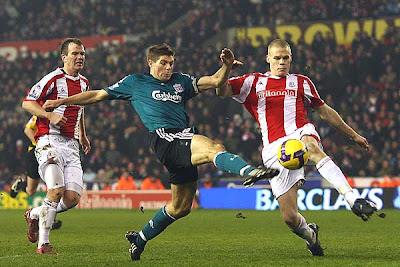 Ryan Shawcross of Stoke City tries to block the shot on goal of Steven Gerrard of Liverpool. He succeeded, as did the Potters in holding the league-leading Reds to a scoreless draw at home.