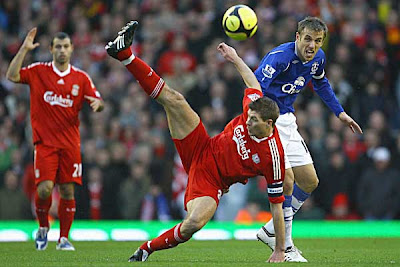 Steven Gerrard of Liverpool competes for the ball with Phil Neville of Everton during their FA Cup Fourth Round match at Anfield on January 25, 2009 in Liverpool, England.