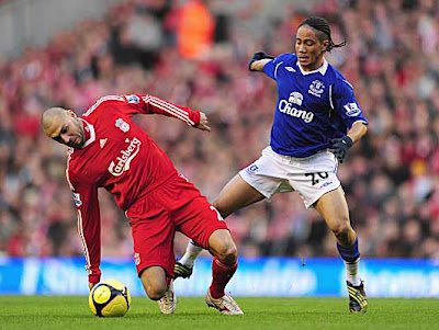 Andrea Dossena of Liverpool is challenged by Steven Pienaar of Everton.