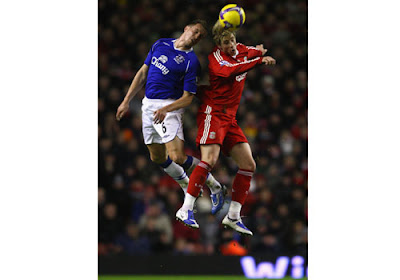Phil Jagielka of Everton leaps for the ball with Fernando Torres of Liverpool