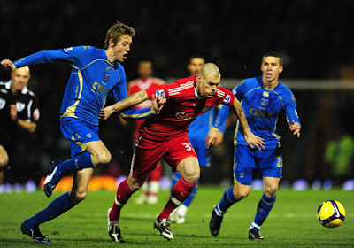 Martin Skrtel of Liverpool is challenged by Peter Crouch of Portsmouth