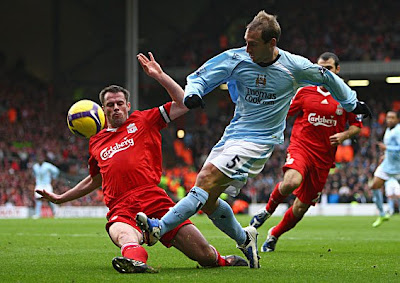 Jamie Carragher of Liverpool tackles Pablo Zabaleta of Manchester City as he attempts to cross the ball.