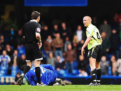 Lee Cattermole (right) of Wigan Athletic is booked by match referee Lee Probert for a foul on Jon Obi Mikel of Chelsea. Chelsea won the tie 2-1.
