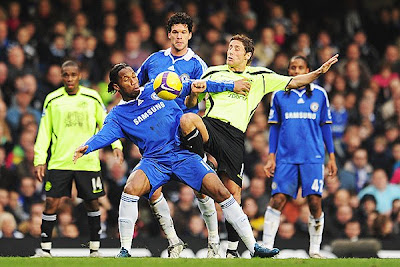 Didier Drogba (left) of Chelsea and Michael Brown (right) of Wigan Athletic challenge for the ball during their match at Stamford Bridge.