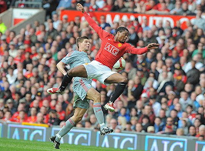 Liverpool's English midfielder Steven Gerrard (left) and Manchester United's French defender Patrice Evra compete for the ball during their English Premier League football match at Old Trafford in Manchester, north west England on March 14, 2009.