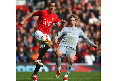 Rio Ferdinand of Manchester United battles for the ball with Fernando Torres of Liverpool