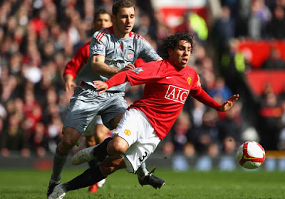 Fabio Aurelio of Liverpool challenges Carlos Tevez of Manchester United