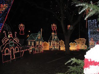 Lighted Christmas village with angels hanging in the background