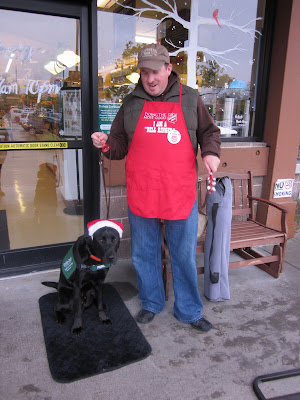 John wearing the Salvation Army apron and ringing bells with Dagan by his side