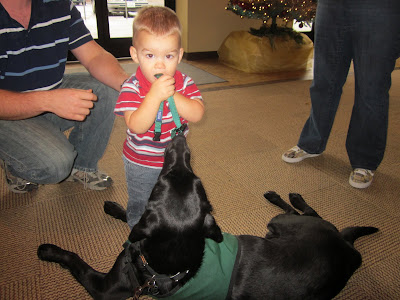 Dagan lying down with a toddler in front of him, holding Dag's GL