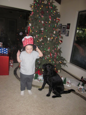 Dagan and 5 year old Brian in front of the tree, Brian wearing a hat shaped like a chimney with Santa's legs kicking out the top