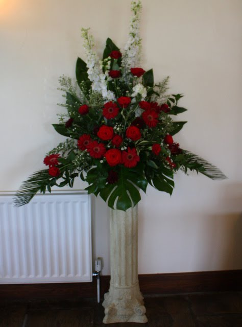 The Burgundy and White Pedestal design of Delphiniums Roses and Gerberas
