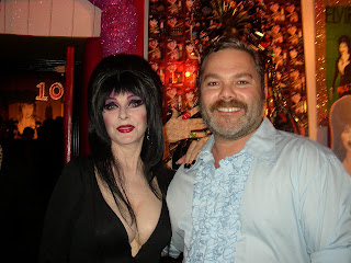 Photo of artist Jason Mecier with Elvira standing in front of her portrait