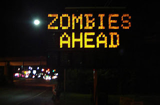 Lighted traffic sign that says Zombies Ahead