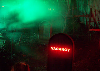 Vacancy tombstone glowing red amongst the other headstones in the cemetary