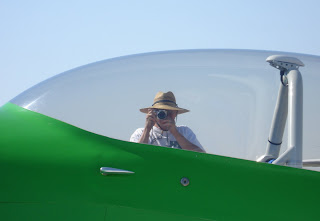photo-of-my-husband-taking-a-photo-of-me-from-other-side-of-green-plane-at-air-show
