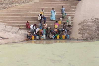 women collecting water from reservoir