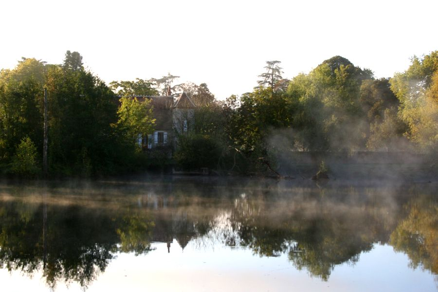 view of house on far bank through mist on river