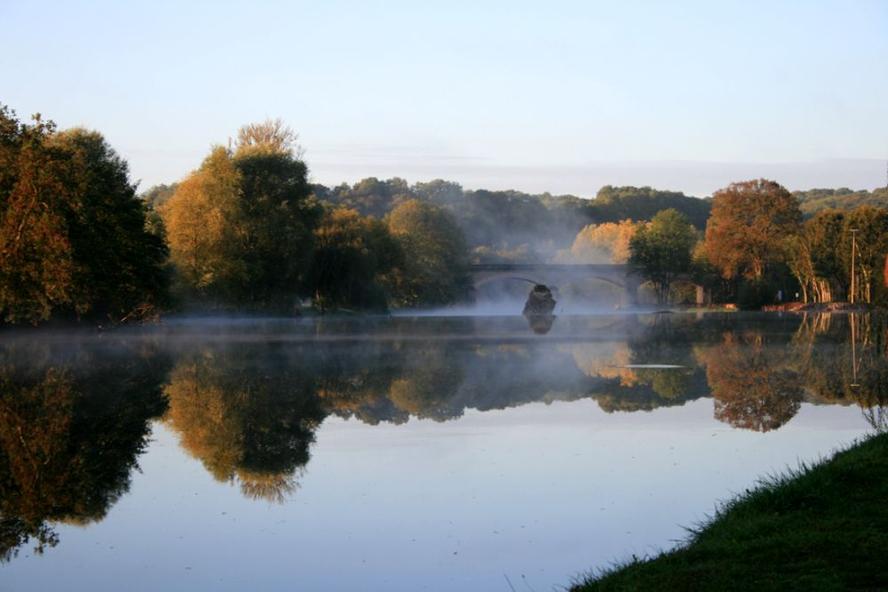 view down river mist rising autumnal trees
