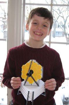 Niño con modelo de papel del JWST