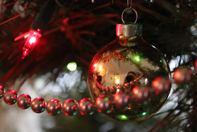 This photo is a close up of my parent's Christmas tree. It highlights a gold reflective Christmas Ball, a gold garland, and a bright small bulb from a multi-colored light strand.