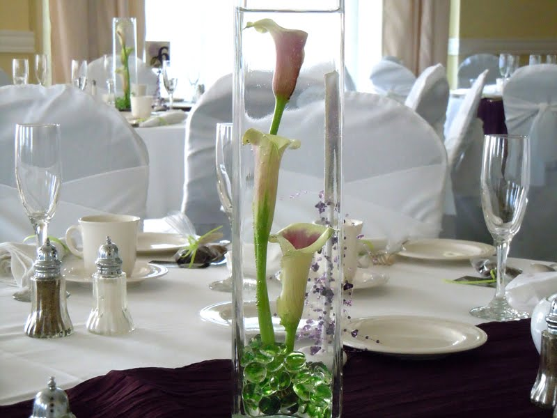 centerpiece of picasso calla lilies in a square glass vase