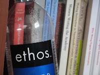 A photo of an Ethos brand water bottle on a bookshelf.