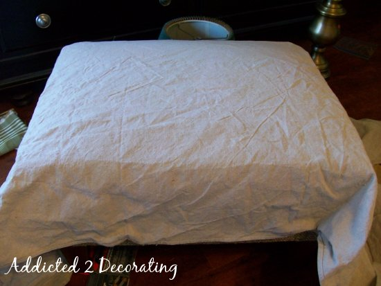 first i draped a large piece of fabric over the ottoman ensuring that it hung down the same length on all four sides