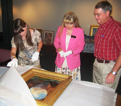 Erica Cottam, Deborah Reeder and Lyman Hafen unwrap the Thomas Moran painting - The Rio virgin Southern Utah, 1917