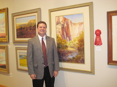 Artist Roland Lee with his painting Solace at Sinawava at the Robert and Peggy Sears Invitational Art Show at Dixie State College of Utah
