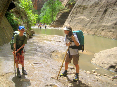 Hikers in Zion Narrows with hiking sticks