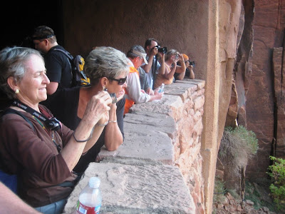 Barbara Aikens and Sandra Sandberg join others looking out the gallery window from the Zion Tunnel