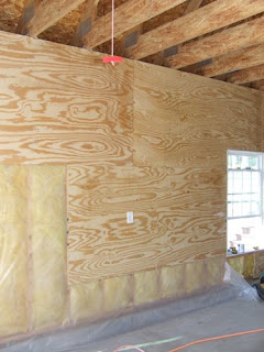 picture of plywood on interior garage walls and fiberglass insulation