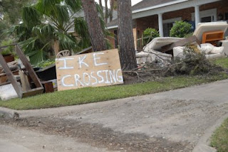 Ike Crossing sign in front of a water-damaged home.