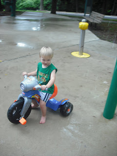 toddler with big wheel at spray fountain