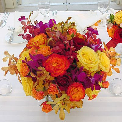 A Vibrant Orange and Yellow Rose Centerpiece with Purple and Yellow Orchids