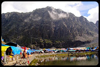 PHOTO JOURNEY to Manimahesh Lake in Pir Panjal Mountain Range of Himalyas : Posted by Vishal Sharma on www.travellingcamera.com : As we have been sharing trekking experiences of Manimahesh Yatra, here is the final destination which is reached after joyful journey on hills through clouds .... Here we are sharing some of the photographs of Manimahesh Lake which is also known as Dal Lake, Manimahesh...Manimahesh Lake is a high altitude lake (elevation 4100 metres) situated close to the Manimahesh Kailash Peak in the Pir Panjal Range of the Himalayas....It's in the Bharmour subdivision of Chamba district of the Indian state of Himachal Pradesh.... The religious significance of this lake is next to that of the Lake Manasarovar in Tibet...The lake is the venue of a highly revered pilgrimage trek undertaken during the month of August/September corresponding to the month of Bhadon according to Hindu calendar... on the eighth day of the New Moon period.... It is known as the 'Manimahesh Yatra'.... The Government of Himachal Pradesh has declared it as a state-level pilgrimage...The lake, of glacial origin, is in the upper reaches of the Budhil River which is a tributary of the Ravi River in Himachal Pradesh....Its also known as 'Manimahesh Ganga'... The stream originates from the lake in the form of a fall at Dhancho...The mountain peak is a snow clad tribal glen of Brahamur in the Chamba district originating as an off-shoot spur of the Pir Panjal Range...The highest peak is the Mani Mahesh Kailas which is also called 'Chamba Kailash' (5650 m)) overlooking the lake... (The one covered with clouds in this photograph..) The lake is considered as a glacial depression which is sourced by snow-melt waters from the surrounding hill slopes...Trekking in the last stretch is through the glacier fields of the lake... but on the way, the walk is through the valley of flowers and wild medicinal herbs up to the lake..... Its is situated at the centre of a snowy field touching the sacred peak.... Manimahesh lake is called Shiv Chaugan (play ground of Lord Shiva)... On a clear day the reflection of the abode of Shiva, the Kailash Mountain can be seen on the lake surface... During most of the time of an year this lake remains desolate, without any inhabitants, because this region gets snofall in most of the duration...  The air is fresh but icy cold... In the periphery of the lake, now there is a marble image of Lord Shiva, which is worshipped by pilgrims. The image is called the Chaumukha. Manimahesh lake and its surroundings present an impressive view. The still, clear and unpolluted waters of the lake reflect the snow-capped peaks that overlook the valley..