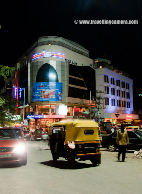 An evening on MG Road of Banglore - During November 2010 : Posted by VJ SHARMA on www.travellingcamera.com : Mahatma Gandhi Road (popularly called as MG Road) is a road in Bangalore, which is capital of Karntaka state of India. It runs east from Trinity Circle at one end to Anil Kumble circle at the other end... Recently I also visited the place and here are few photographs.. : I am sure that I need not to explain about the traffic conditions of the city... I have seen worst traffic conditions in banglore the conditions are not same on all the roads every time but still it wastes lot of time... Few roads inside the city are very narrow and traffic is increasing day by day...MG Road used to be known as South Parade before independence of India. Later it was renamed as Mahatma Gandhi Road during 1948s...Unlike Delhi, cycle-rikshaws are not there in the city. I am not sure about the reason but probably traffic. These slow moving means of conveyance may slow down the traffic further... So Auto-Raikshwas is the only option apart from public Transport.. During the visit I tried  both types of buses which run inside the city.. Normal bus and few AC buses... and noticed and must thing in those buses that driver has the control to open the door whenever it stops at a particular bus-stand. Then it automatically closes and passengers can't open the door... Nice thing which should be a must feature in India...There are lot of good showrooms on MG Road and most of the brands, restaurants are available on one side of the road... We came to MG road during the evening after having a nice visit to Banerghatta National Park... We had some snacks at KFC and started roaming around the places there....MG Road is also one of the busiest roads in Banglore city and is lined on one side with various showrooms, food outlets and restaurants etc. It has many office buildings, shops and theaters as well. MG Road is also a pace to look for large number of buildings and banks...On the other side of the road, Metro work was going on and they had places a model of the metro train which is planned to run on these tracks.... People go to see these coaches and also click some photographs with it....Every one in the city is waiting for Metro to start and improve the connectivity of East Banglore with West part !!! The road has been converted into one way ... Commuters traveling towards MG Road from Anil Kumble Junction will have to turn towards Cubbon Road and go towards Manipal Centre & further on to Trinity Junction due to the construction of Metro Track...The famous Hard Rock Cafe of Banglore !!! Its on the other side of the road....MG Road is adjacent to the Museum Road and perpendicular to Brigade Road... It is also pretty close to a shopping area called Commercial Street...Another Photograph of Hard Rock Cafe from other side of the road in Banglore...A Photograph showing traffic conditions on MG Road of Banglore City...Now it was time to move towards Brigade Road which are perpendicular to MG Road in Banglore.... I will few more photographs spcific to Brigade road and its main attractions... Pub Street n all !!!Mcdonalds in native script of Karnataka.. I saw this first time.... Even companies like Oracle had mentioned their name in Kannada ...