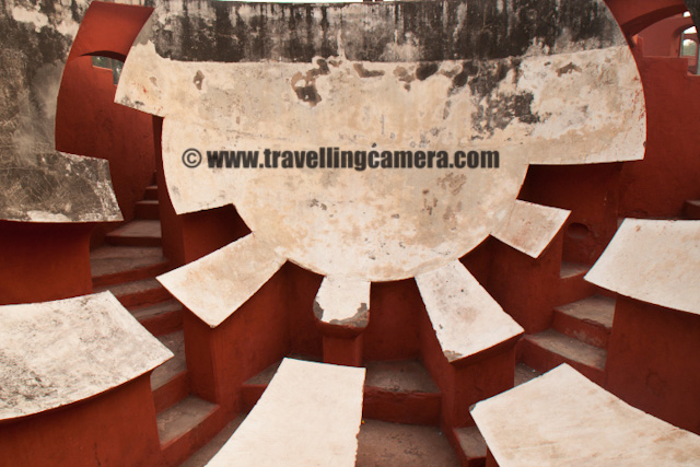 A Quick visit to Jantar Mantar in Capital City of India - Delhi : Posted by VJ SHARMA on www.travellingcamera.com : The Yantra Mantra which literally means 'instrument and formula' and often called as Jantar Mantar... There are multiple Jantar Mantars in India and Delhi has also one near Connaught Place.... Jantar Mantar in Delhi consists of 13 architectural astronomy instruments which were built by Maharaja Jai Singh 2 of Jaipur... Some of my friends decided to meet on weekend at CP but few of them were late... We were only two at that time and though of roaming around the place and reached at Jantar Mantar... I have been to Jantar Mantar at Jaipur and the one in Delhi seemed smaller as compared to that... Check out some of the photographs of Jantar Manatar @ Delhi...Here is a photograph of one of the yantra to predict time with respect to the movement of sun and shadows.... Its really amazing work... There are lot of yantras there and each one solves a particular problem.... Sometimes calculations from one are used in conjunction with the calculations from other to draw some more useful conclusions... Its hard to believe that such a great scientific work are available in 17s....Here is the main architectural form which we normally saw in most of the photographs of Jantar Mantar... Most of the times its very crowded and I had to wait for approximately 25 minutes to have these two people walking in front of it... Most of the times 50+ people can be found around this yantra and have some photographs....Ram Yantra at Jantar Mantar, DelhiInitially Jai singh had started building these from Brass but soon they realized some bad impacts of the metal and revisited the though of selecting other construction material... Main purpose of these observatories was to compile astronomical tables and to predict the times, movements of the sun, moon & planets. Some of these purposes nowadays would be classified as astrology... Its one of the main places to visit in Delhi and amazing work which completed in 1724....Indian Policemen doing something in lawns of Jantar Mantar, Delhi, INDIAApart from Delhi, the other Jantar Mantars are there is Jaipur, Varanasi, Ujjain and Mathura....